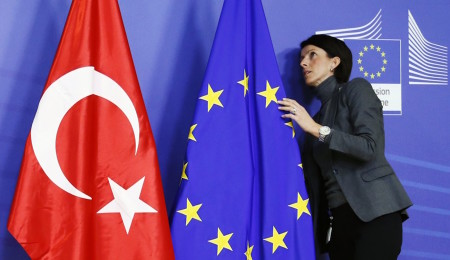 A staff adjusts European Union and Turkish (L) flags ahead of the arrival of Turkey's Prime Minister Tayyip Erdogan (not pictured) at the EU Commission headquarters in Brussels January 21, 2014. REUTERS/Francois Lenoir (BELGIUM - Tags: POLITICS)